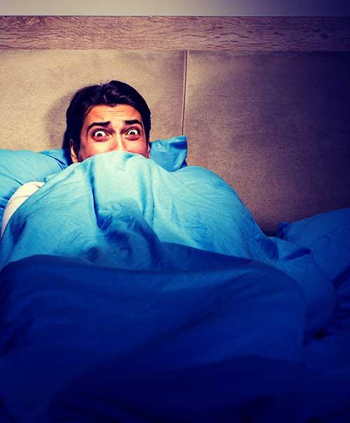 Homme terrorisé dans son lit après avoir vu l'exorciste.