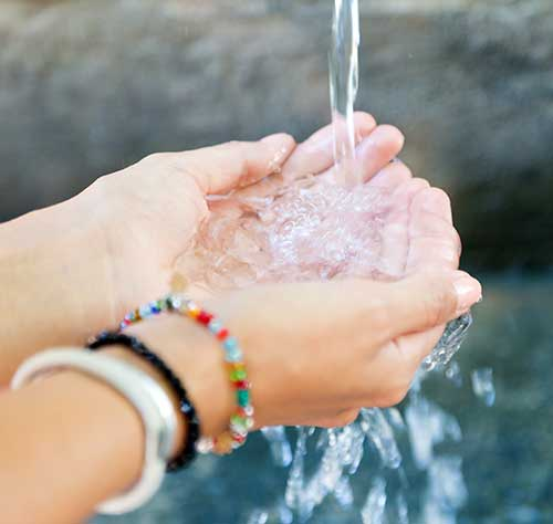 Une femme se lave les mains avec de l'eau.