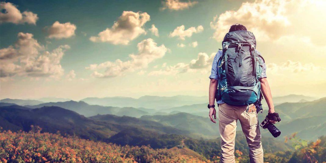 Jeune homme au sommet d'une montagne avec un sac à dos et un appareil photo. Découverte magazine.