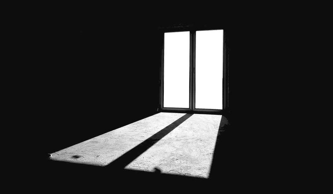 Pièce sombre avec fenêtre qui inonde de lumière.